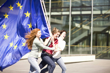 Young girls laughing and walking holding an EU flag