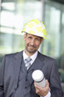 Portrait of mature man in suit wearing hardhat and holding tube container