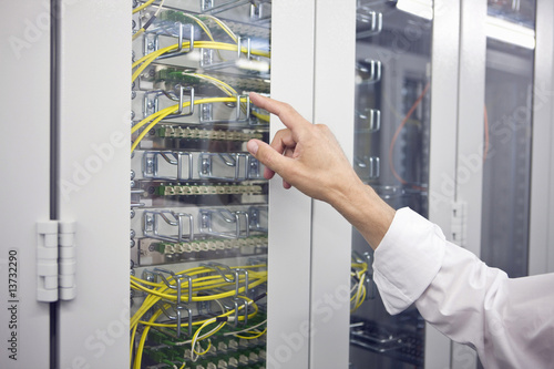 Detail of computer server with hand pointing to it