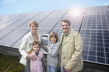 Happy family standing in front of solar paneling, Munich, Germany