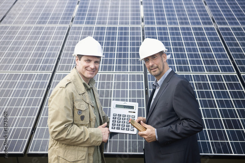 Mature businessmen holding a calculator in front of solar paneling, Munich, Bavaria, Germany