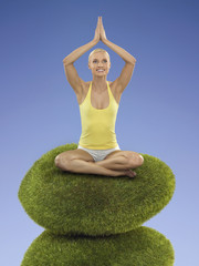 Portrait of young adult woman practicing yoga on a shrub, studio shot