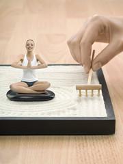 Portrait of young adult woman meditating in desktop Zen garden, digital composite