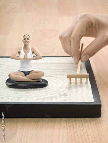 Portrait of young adult woman meditating in desktop Zen garden, digital composite