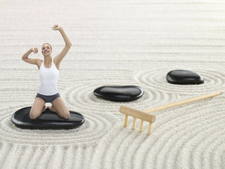 Portrait of young adult woman meditating in Zen garden, digital composite