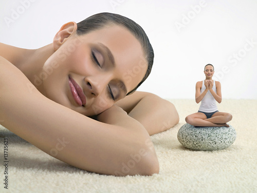 Portrait of young woman asleep next to a young woman practicing yoga, digital composite