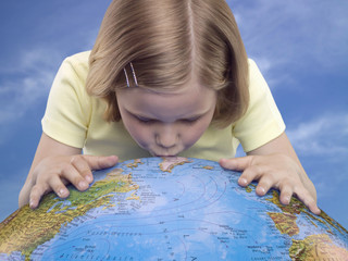 Young girl kissing a globe, studio shot