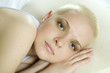 attractive thoughtful blond bald woman lying on the bed