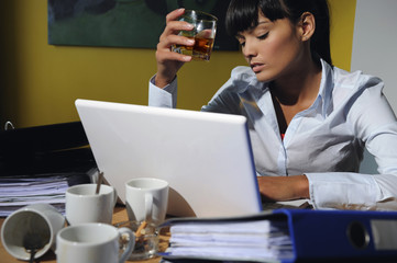 Portrait of woman drinking alcohol at work