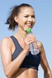 Sportliche Frau mir Trinkflasche am Strand