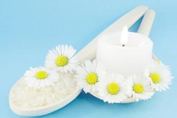 daisies and bath salt over blue
