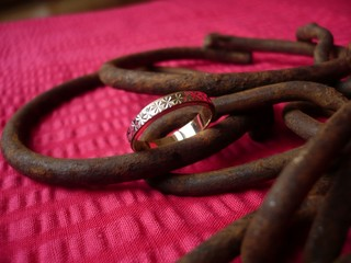 wedding ring and ferruginous chains on a red background