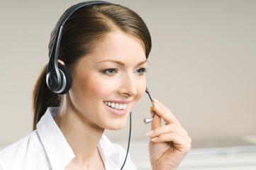 Attrakitve Frau arbeitet mit Headset im Call-Center