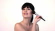 Young beautiful woman is doing makeup with brush