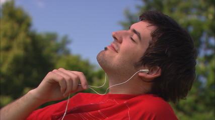 junger mann hört musik mit mp3-player