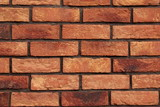 A brick wall made of red and orange brick