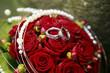 Trauringe auf einem Brautstrauß roter Rosen
