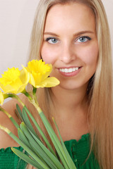 Beautiful blond woman with yellow flowers isolated on white