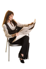 Business woman reading a newspaper on the chair