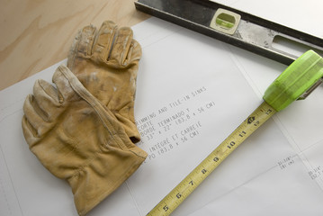 construction plans with gloves and tools