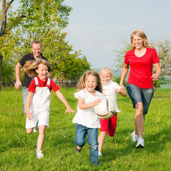 Familie spielt Ball auf einer Wiese