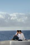 Fototapety couple assis sur un mur face à la mer