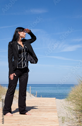 zest woman standing in formal clothes on the beach on boardwalk