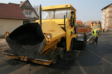 Machinery and workers repairin asphalt road