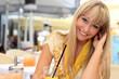 schöne junge blonde Frau im Strassencafe mit Fruchtsaft
