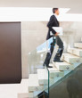 Blur motion: Business man walking up a flight of stairs