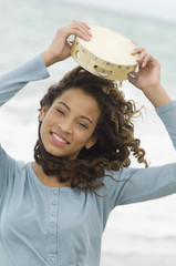 Portrait of a girl holding a tambourine over her head