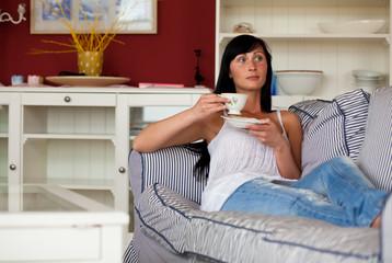 frau beim wohlfühlen und aufwärmen auf der couch mit tee