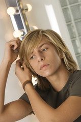 Teenage boy combing his hair