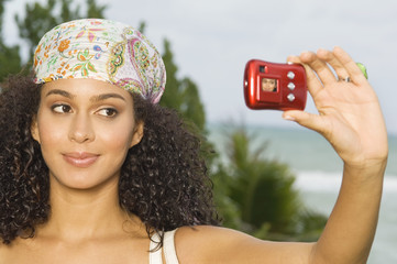 Woman taking a picture of herself with a digital camera
