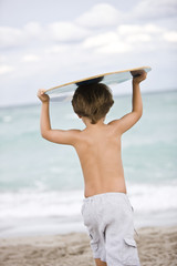 Rear view of a boy holding a body board over his head