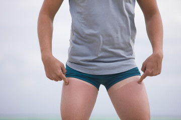 Man showing tan lines on his thighs
