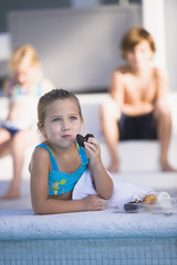 Girl eating chocolate donut at the poolside