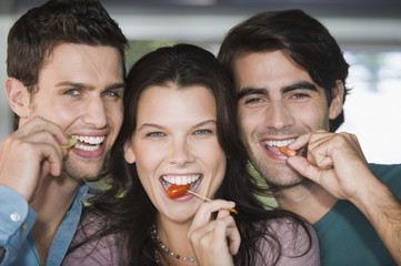Portrait of three friends eating fruits