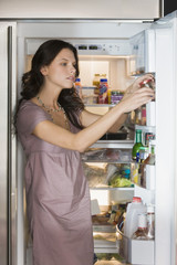 Woman taking out a bottle from a refrigerator