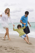 Couple playing with their son on the beach