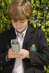Boy text messaging with a mobile phone