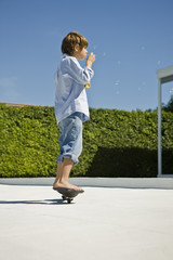 Boy blowing bubbles with a bubble wand while skateboarding