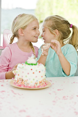 Two girls smiling in front of a birthday cake