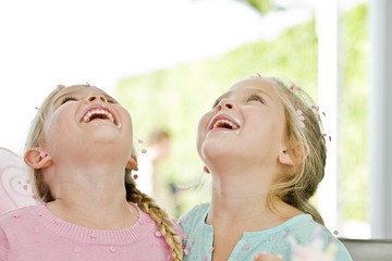Close-up of two girls looking up and laughing