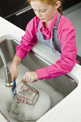 High angle view of a girl washing a measuring jug at a sink