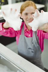 Portrait of a girl showing her hands covered in soap suds