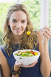 Portrait of a woman eating fruit salad
