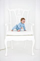 Baby boy sitting in an armchair