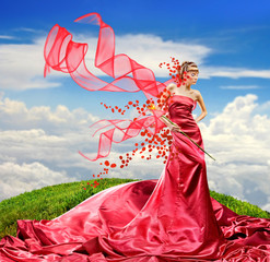 Beautiful girl in a long red dress holds exotic flower in a hand