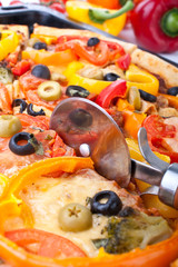 cutting vegetable pizza with a pizza-knife